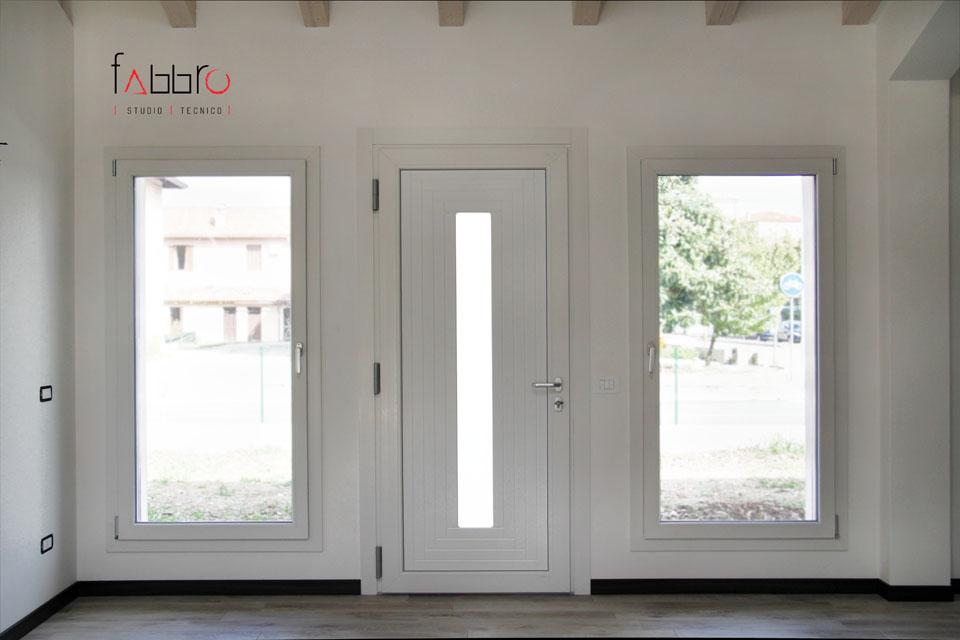 studio tecnico fabbro ingresso con porta bianca e vetrate ai lati con infissi chiari